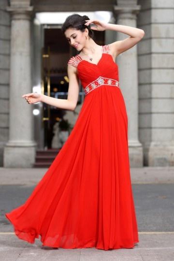 Robe de soirée rouge décolleté en V Empire parée de bijoux