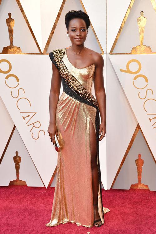 Lupita N'yongo porte une robe de soirée fendue dorée asymétrique orné de strass
