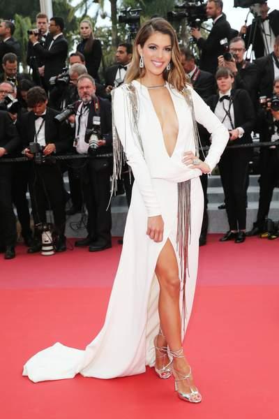 Iris Mittenaere en une robe de soirée blanche fendue col décolleté en V plongeant à manche longue