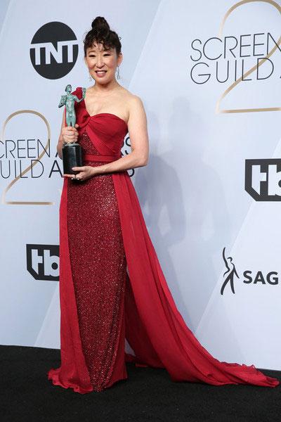 Sandra Oh en une robe de soirée rouge asymétrique longue orné de paillettes